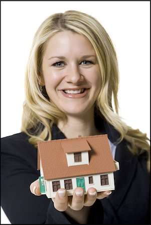 Woman holding a toy house Stock Photo - Premium Royalty-Free, Code: 640-03265384