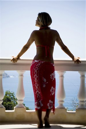 Woman on balcony overlooking ocean Stock Photo - Premium Royalty-Free, Code: 640-03265495