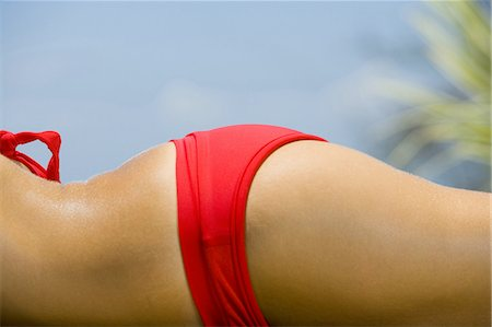 Mid section view of a adult woman sunbathing Stock Photo - Premium Royalty-Free, Code: 640-03265646