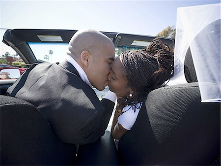 Rear view of a newlywed couple kissing each other in a car Stock Photo - Premium Royalty-Free, Code: 640-03265664