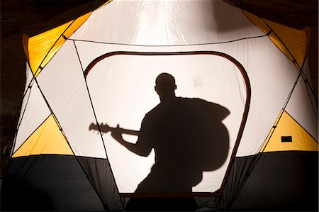 People singing and playing guitar in tent Stock Photo - Premium Royalty-Free, Code: 640-03260311