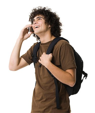 Teenage boy talking on cell phone holding backpack Stock Photo - Premium Royalty-Free, Code: 640-03260747