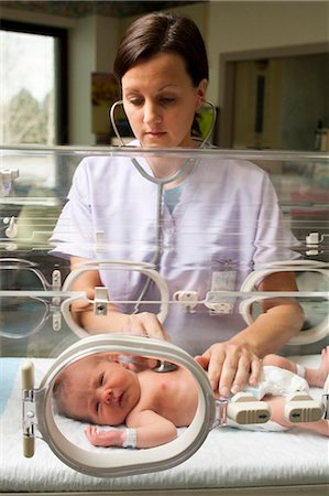 Nurse examining newborn in incubator Stock Photo - Premium Royalty-Free, Code: 640-03261667