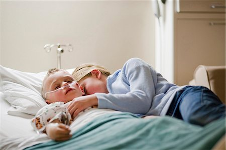 Girl laying with brother on hospital bed Stock Photo - Premium Royalty-Free, Code: 640-03261661