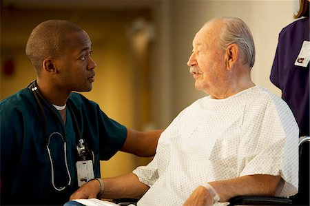 Mature man in wheelchair with doctor and nurse Stock Photo - Premium Royalty-Free, Code: 640-03261745