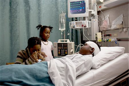 Family watching boy in hospital bed with head bandages Stock Photo - Premium Royalty-Free, Code: 640-03261817