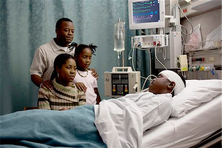 Family watching boy in hospital bed with head bandages Stock Photo - Premium Royalty-Free, Code: 640-03261818