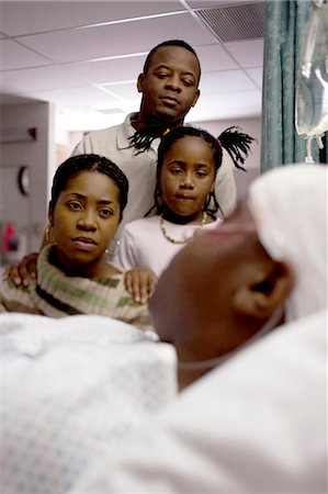Family watching boy in hospital bed with head bandages Stock Photo - Premium Royalty-Free, Code: 640-03261819