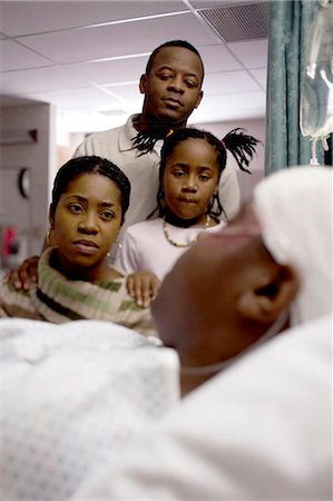 Family watching boy in hospital bed with head bandages Stock Photo - Premium Royalty-Free, Code: 640-03261820