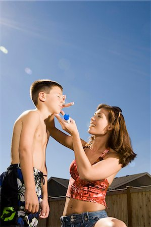 Woman applying sunscreen lotion to boy's face Stock Photo - Premium Royalty-Free, Code: 640-03262791