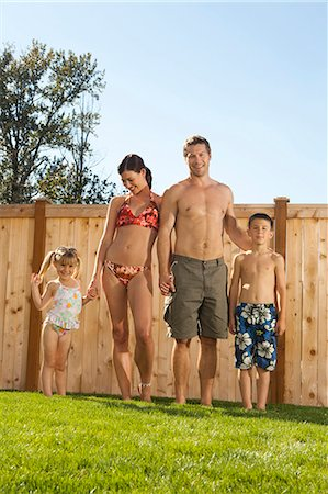 father son bath - Family in bathing suits holding hands in yard Stock Photo - Premium Royalty-Free, Code: 640-03262819