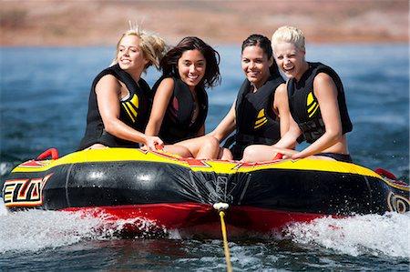 Four women on inner tube wearing life jackets Stock Photo - Premium Royalty-Free, Code: 640-03263189