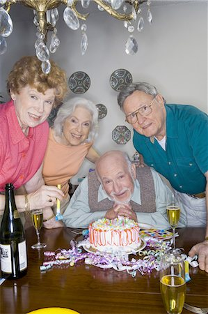 Partygoers around a birthday cake Stock Photo - Premium Royalty-Free, Code: 640-03281683