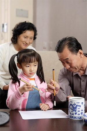 Grandfather and Grandmother practising Chinese calligraphy with granddaughter Stock Photo - Premium Royalty-Free, Code: 642-01735340