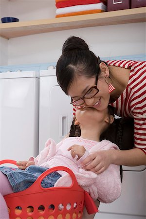 daughter kissing mother - Girl sitting on basket and kissing Mom Stock Photo - Premium Royalty-Free, Code: 642-01736674