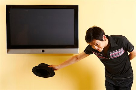plasma - Fashionable young man bowing in front of TV Stock Photo - Premium Royalty-Free, Code: 642-01736857