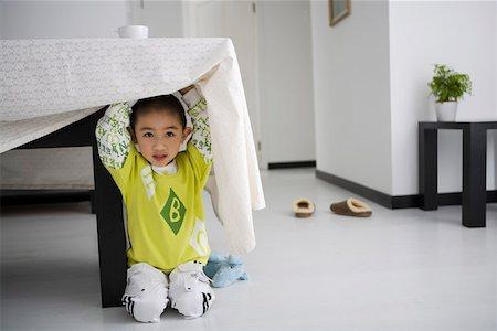 Boy hiding under table, smiling Stock Photo - Premium Royalty-Free, Code: 642-01732839