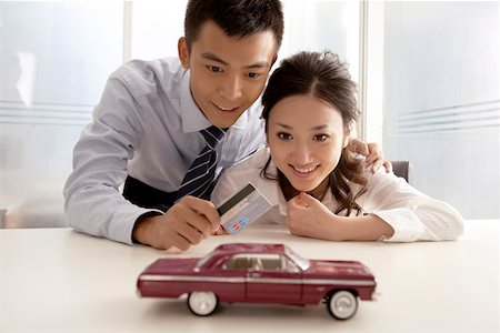 Young man and young woman looking at credit and car model Stock Photo - Premium Royalty-Free, Code: 642-01733259