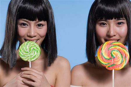 two fashionable girls eating lollipops Stock Photo - Premium Royalty-Free, Code: 642-02005999
