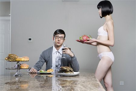 a business man who is eating fruits and a bikini girl Stock Photo - Premium Royalty-Free, Code: 642-02006021