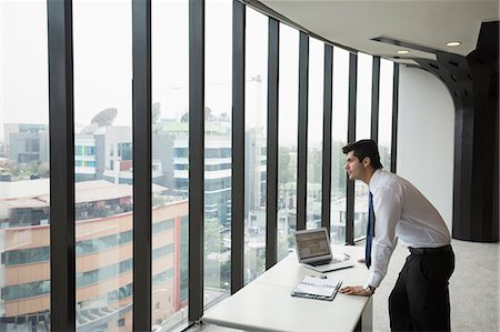 east indian (male) - India, Businessman standing by desk and looking through window in office Stock Photo - Premium Royalty-Free, Code: 655-08357106