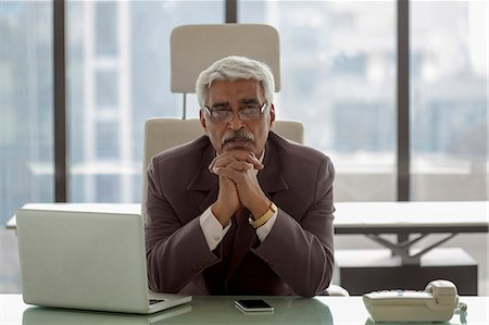 India, Portrait of senior businessman siting at desk with hands under chin Stock Photo - Premium Royalty-Free, Code: 655-08357155