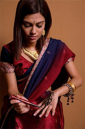 singapore traditional costume lady - Indian woman painting hand with henna Stock Photo - Premium Royalty-Free, Code: 655-02375864