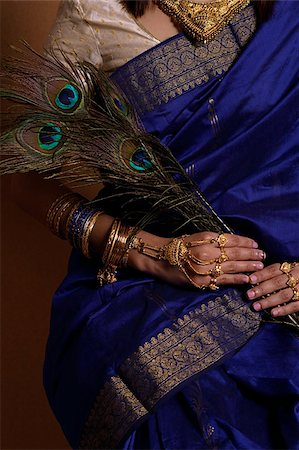 singapore traditional costume lady - Torso of Indian woman holding peacock feathers Stock Photo - Premium Royalty-Free, Code: 655-02375866