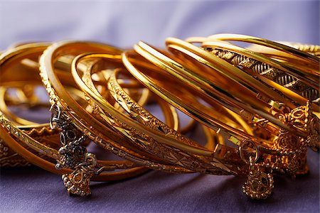 expensive jewelry - gold Indian bangles on purple sari cloth Stock Photo - Premium Royalty-Free, Code: 655-02703059
