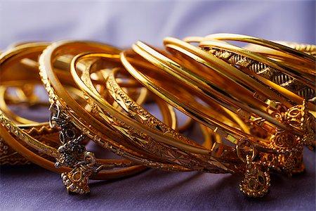 expensive jewelry - gold Indian bangles on purple sari cloth Stock Photo - Premium Royalty-Free, Code: 655-02703059