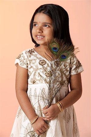 Little girl wearing traditional Indian clothing holding peacock feathers Stock Photo - Premium Royalty-Free, Code: 655-02883050