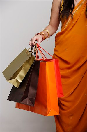 singapore traditional costume lady - Woman wearing sari holding shopping bags Stock Photo - Premium Royalty-Free, Code: 655-03082794