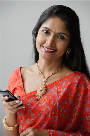 singapore traditional costume lady - Indian woman wearing a sari and using a mobile phone Stock Photo - Premium Royalty-Free, Code: 655-03241644