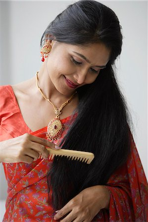 singapore traditional costume lady - Indian woman wearing a sari and combing her hair Stock Photo - Premium Royalty-Free, Code: 655-03241651