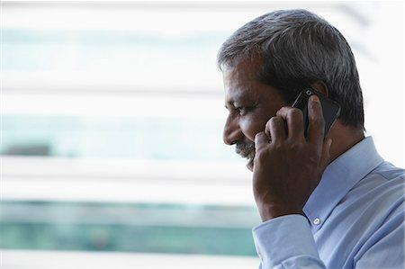 Head shot of mature Indian man talking on phone Stock Photo - Premium Royalty-Free, Code: 655-03457916