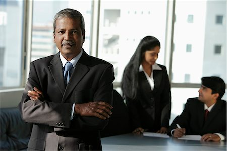 Mature Indian man standing in front of his colleages Stock Photo - Premium Royalty-Free, Code: 655-03458039