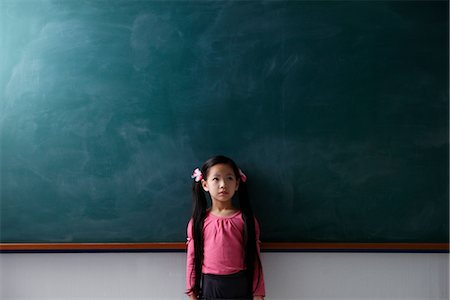 Young girl with pony tails standing in front of a chalk board Stock Photo - Premium Royalty-Free, Code: 656-04926615