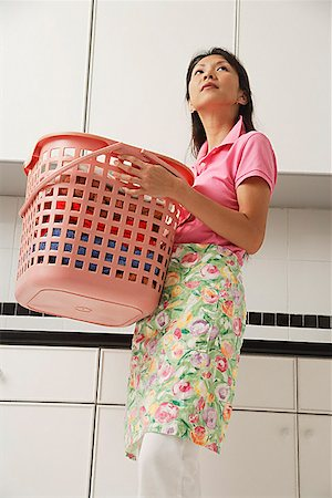 rubber apron woman - Woman doing laundry, holding laundry basket and wearing apron Stock Photo - Premium Royalty-Free, Code: 656-01765424