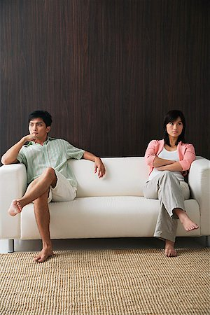 sad lovers break up - Young couple sitting on opposite ends of the sofa Stock Photo - Premium Royalty-Free, Code: 656-01766735