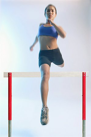 Woman running and jumping over hurdle Stock Photo - Premium Royalty-Free, Code: 656-01767945