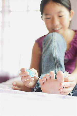 Girl applying nail polish to toenails Stock Photo - Premium Royalty-Free, Code: 656-01770898