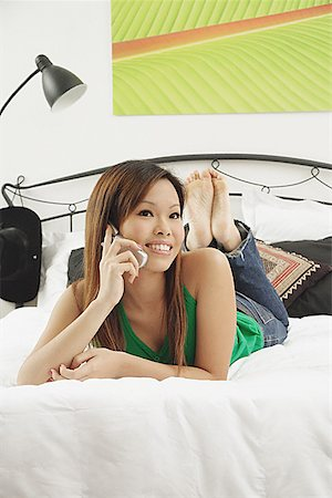 Girl in bedroom, lying on bed, using mobile phone, looking at camera Stock Photo - Premium Royalty-Free, Code: 656-01771222