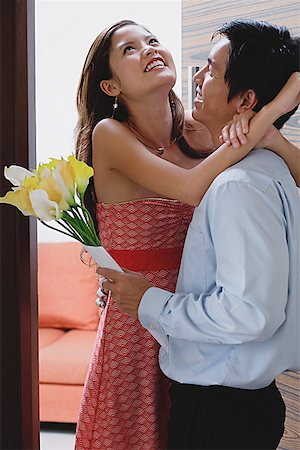 flower greeting - Couple at doorway, man holding flowers, woman embracing him Stock Photo - Premium Royalty-Free, Code: 656-01773456