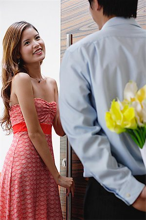 flower greeting - Woman opening door for man, man hiding flowers behind his back Stock Photo - Premium Royalty-Free, Code: 656-01773457