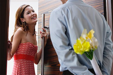 flower greeting - Woman opening door, man with flowers behind his back Stock Photo - Premium Royalty-Free, Code: 656-01773458