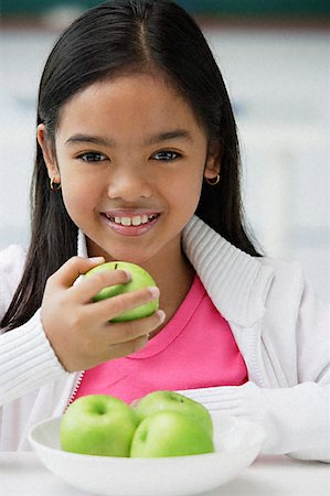 preteen  smile  one  alone - Girl holding green apple in one hand smiling at camera Stock Photo - Premium Royalty-Free, Code: 656-01828897