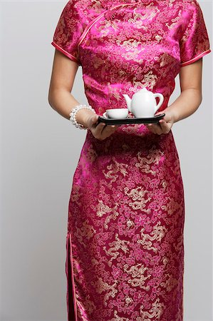 singapore traditional costume lady - Cropped shot of woman wearing a pink cheongsam holding tea Stock Photo - Premium Royalty-Free, Code: 656-03076241