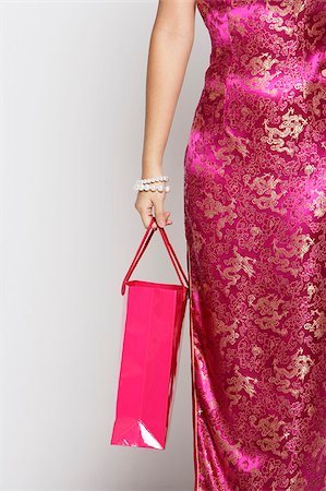 singapore traditional costume lady - Cropped shot of woman in pink cheongsam holding shopping bag Stock Photo - Premium Royalty-Free, Code: 656-03076259
