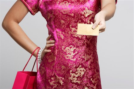 singapore traditional costume lady - Woman in pink cheongsam holding credit card Stock Photo - Premium Royalty-Free, Code: 656-03076276