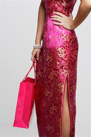 singapore traditional costume lady - Cropped shot of woman wearing a pink cheongsam holding a shopping bag Stock Photo - Premium Royalty-Free, Code: 656-03076285